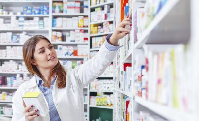 Photo of a professional pharmacist checking stock in an aisle of